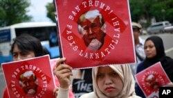 Para aktivis memprotes kebijakan imigrasi Presiden AS Donald Trump di luar Kedutaan Besar AS di Jakarta (4/2). (AP/Dita Alangkara)