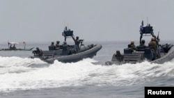 "FILE - U.S. and Philippine Navy servicemen aboard patrol boats conduct a boat manoeuvre exercise past a fishing boat during a joint annual military exercise called ""Carat"" at the former U.S. military base Sangley Point in Cavite city, west of Manila, June"