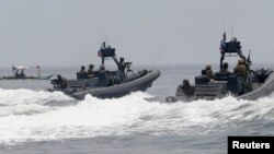 """FILE - U.S. and Philippine Navy servicemen aboard patrol boats conduct a boat manoeuvre exercise past a fishing boat during a joint annual military exercise called """"Carat"""" at the former U.S. military base Sangley Point in Cavite city, west of Manila, June"""