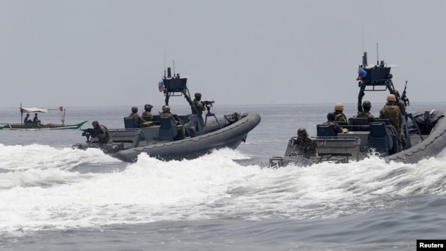 FILE - U.S. and Philippine Navy servicemen aboard patrol boats conduct a boat manoeuvre exercise past a fishing boat during a joint annual military exercise called