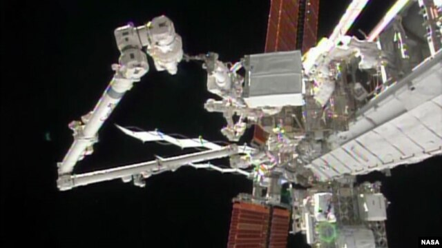 Astronaut Rick Mastracchio holds the degraded pump module while the International Space Station's robotic arm guides the module to a grapple fixture. (Credit: NASA TV)
