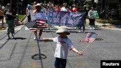 Un niño con la bandera estadounidense en la mano participa de un desfile.