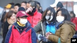 People stand in line at a bus terminal in Sendai, Miyagi prefecture on March 16, 2011.