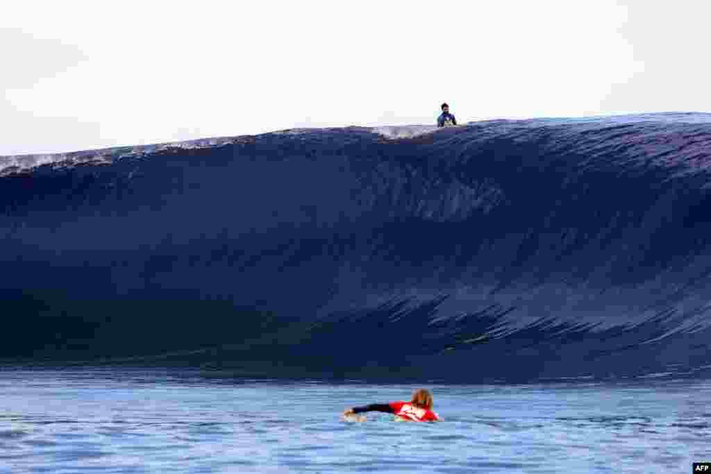 Kai Otton của Australia bơi bên dưới con sóng trong khi Dion Atkinson của Australia lướt bên trên trong ngày trình diễn cuối cùng của sự kiện lướt sóng ấn Billabong Pro Tahiti lần thứ 14, một phần trong tour biểu diễn vòng quanh thế giới của Hiệp hội Người lướt sóng Chuyên nghiệp ở Teahupoo, trên đảo Tahiti thuộc quần đảo Polynesia thuộc Pháp, ngày 25 tháng 8, 2014.