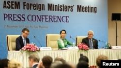 Penasihat Negara Myanmar Aung San Suu Kyi memberikan keretangan kepada media dalam konferensi pers bersama Menteri Luar Negeri Estonia Sven Mikser (kiri) dan Sekretaris Kementerian Luar Negeri Spanyol Ildefonso Castro (kanan) di kantor Menteri Luar Negeri Asia Eropa (ASEM) di Naypyitaw, Myanmar, 21 November 2017.
