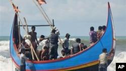 Penjaga pantai Bangladesh memeriksa pengungsi muslim Rohingya yang selamat dari kapal mereka yang tenggelam di lepas pantai Bangladesh (7/11).