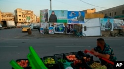 FILE - A street vendor who sells fruits passes by campaign posters for upcoming parliamentary elections in Baghdad, Iraq, Oct. 7, 2021.