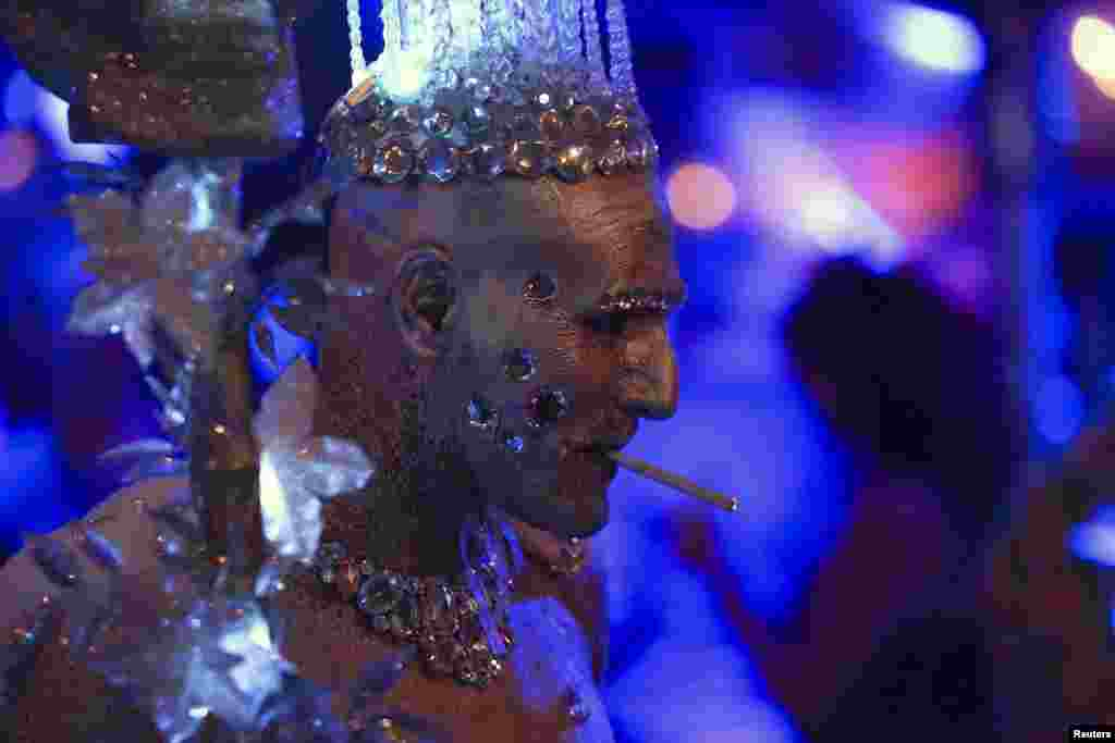 A man dressed as an ice queen smokes a cigarette during the West Hollywood Halloween Costume Carnaval, which attracts nearly 500,000 people annually in West Hollywood, California, Oct. 31, 2013.