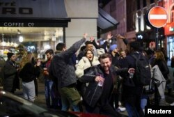 A group of people dance as they party on a street in Soho, as the coronavirus disease (COVID-19) restrictions ease, in London, Britain April 12, 2021.