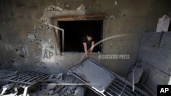 A Lebanese man removes debris from his damaged house, hit by rockets fired by Syrian rebels according to villagers, in Hermel town, northeast of Lebanon, Wednesday May 29, 2013. Shells fire from Syria regularly strike the Lebanese northeastern town of Her