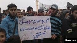 Người Syria cầm biểu ngữ với hàng chữ 'Mùa xuân Ả Rập sẽ biến al-Assad thành bong bóng xà phòng và sẽ biến mất' trong cuộc biểu tình tại Habeet gần Idlib, ngày 6/1/2013. Tại Syria, các nhà báo và người sử dụng internet là nạn nhân của một 'cuộc chiến tranh thông tin' được thực hiện bởi chính phủ Assad.