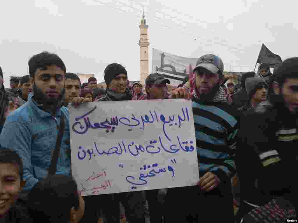 "Demonstrators hold a sign that reads ""The Arab spring will turn you (Syrian President Bashar al-Assad) into soap bubbles that will disappear"" during a protest in Habeet near Idlib, Syria, January 6, 2013."