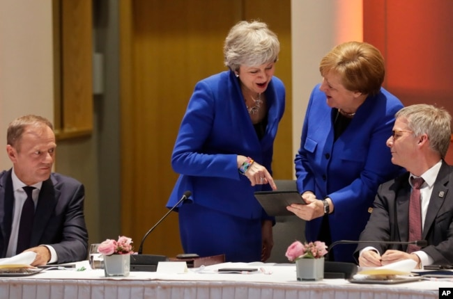 European Council President Donald Tusk, left, looks on as British Prime Minister Theresa May, center left, and German Chancellor Angela Merkel, center right, view a tablet during a meeting at an EU summit in Brussels, April 10, 2019.