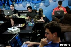 "Zander Dejah (2nd L), 25, who works as a Virtual Reality engineer, Nick Olszowy (C), 25, a software engineer and Andrew Bresee, 26, a software engineer, all who are residents of The Negev tech house, use their electronics during a Sunday ""family"" dinner i"