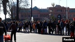 People line up in front of the Casa Rosada Government House to receive free pears and apples during a protest staged by Argentine producers and farmers from the Patagonian provinces of Neuquen and Rio Negro for their losses in Buenos Aires, Argentina, Aug. 23, 2016.