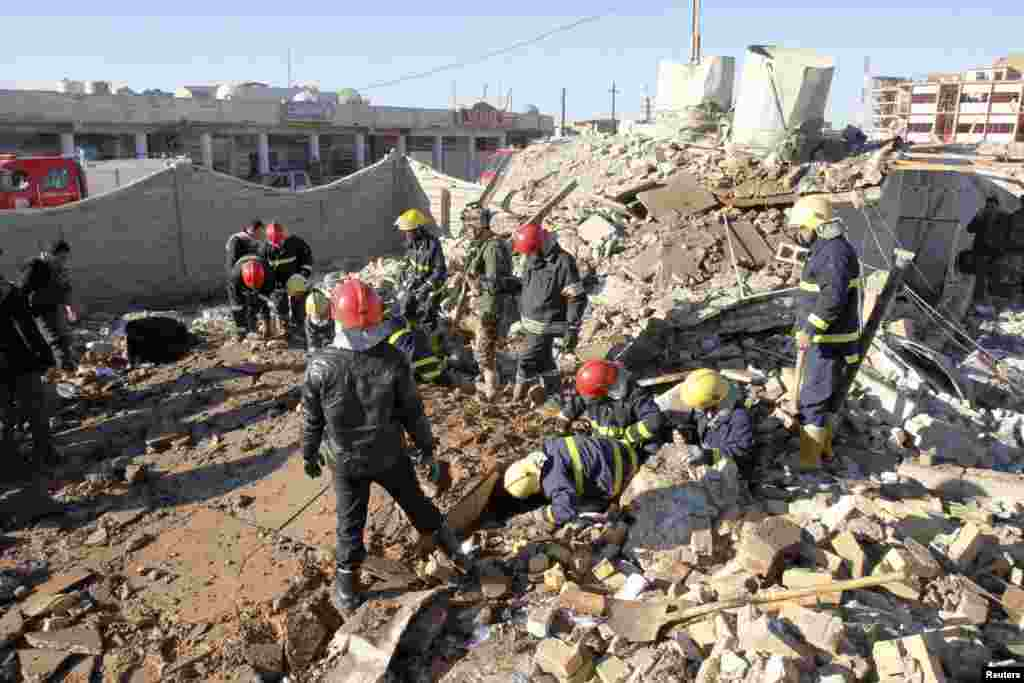 Iraqi civil defense personnel inspect a damaged building after a suicide attack in Kirkuk, Iraq, January 16, 2013.