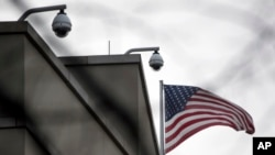 FILE - An American flag flutters beside CCTV cameras on top of the U.S. embassy in Berlin, Germany, Oct. 25, 2013.