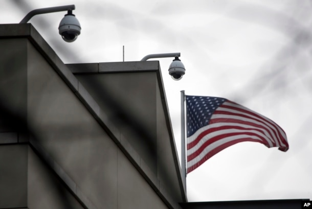 American flag waves beside CCTV cameras on top of the U.S. embassy in Berlin, Germany, Oct. 25, 2013.