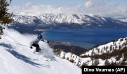 With Lake Tahoe as a backdrop, a skier kicks up some powder at Heavenly Ski Resort, Wednesday, April 14, 2010 in South Lake Tahoe, Calif