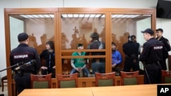 From left: Temirlan Eskerkhanov, Shadid Gubashev, Khamzat Bakhayev, Anzor Gubashev and Zaur Dadayev — defendants suspected of involvement in the killing of opposition leader Boris Nemtsov — stand in a glass enclosure during their trial in a Moscow military district court in Moscow, Russia, June 27, 2017.
