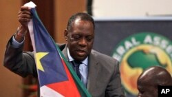 Confederation of African Football (CAF) president Issa Hayatou, left, receives South Sudan's national flag from its federation president Oliver Benjamin, right, during the Confederation of African Football General Assembly in Libreville, Gabon, Friday Feb