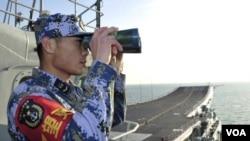 """2013年11月26日,中國海軍""""遼寧號""""航空母艦在南中國海試航期間,一名執勤水兵在甲板上瞭望。"""