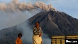 Seorang ibu berjalan sementara Gunung Sinabung memuntahkan debu, 29 November 2013.