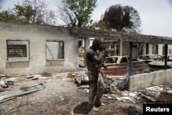 FILE - A soldier walks through the burnt building at the headquarters of Michika local government in Michika town, after the Nigerian military recaptured it from Boko Haram, in Adamawa state, May 10, 2015.