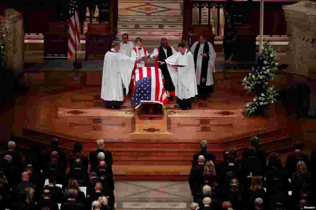 Members of the clergy bless the flag-draped casket of former President George H.W. Bush at the conclusion of his state funeral in the Washington National Cathedral in Washington, Dec. 5, 2018.