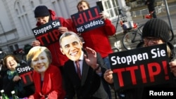 Protesters wear masks of U.S. President Barack Obama and German Chancellor Angela Merkel as they demonstrate against the Transatlantic Trade and Investment Partnership (T-TIP) free trade pact at the Hannover Messe in Hannover, Germany, April 24, 2016.