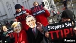 Demonstran anti perjanjian perdagangan Transatlantik memakai topeng Barack Obama dan Angela Merkel di Hannover, Jerman. (Foto: Dok)
