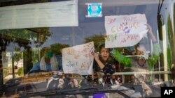 Aktivis India memegang spanduk dan meneriakkan slogan-slogan dari dalam bus setelah ditahan saat melancarkan aksi protes di New Delhi, India, Rabu, 30 September 2020.