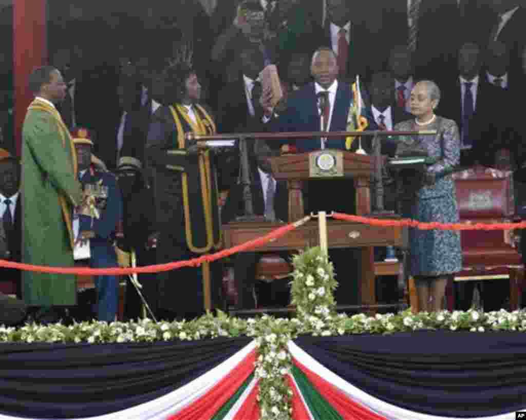 Madaxweyne Uhuru Kenyatta oo gacanta ku haya bible iyadoo loo dhaarinayo xilka madaxweynaha 4aad ee Jamhuuriyadda Kenya waxaana hareer taagan xaaskiisa Margaret Uhuru.