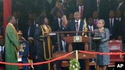 Presiden terpilih Kenya Uhuru Kenyatta didampingi istrinya, Margaret Uhuru (kanan), memegang kitab suci dengan tangan kanannya saat pengambilan sumpah sebagai Presiden Kenya ke-4 di Kompleks Olahraga Internasional Moi di Nairobi, Kenya (9/4).