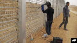 African migrants work at the site where Israel builds a barrier along the border with Egypt in southern Israel, February 15, 2012.