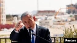 FILE - Israeli Prime Minister Benjamin Netanyahu delivers a statement in front of new construction, in the Jewish settlement known to Israelis as Har Homa and to Palestinians as Jabal Abu Ghneim, in an area of the West Bank that Israel captured in a 1967 war and annexed to the city of Jerusalem, March 16, 2015.