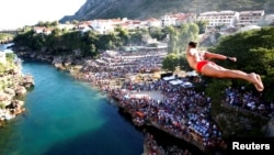 """A man """"takes a plunge"""" from the Old Bridge during 450th traditional diving competition in Mostar, Bosnia and Herzegovina, July 31, 2016."""