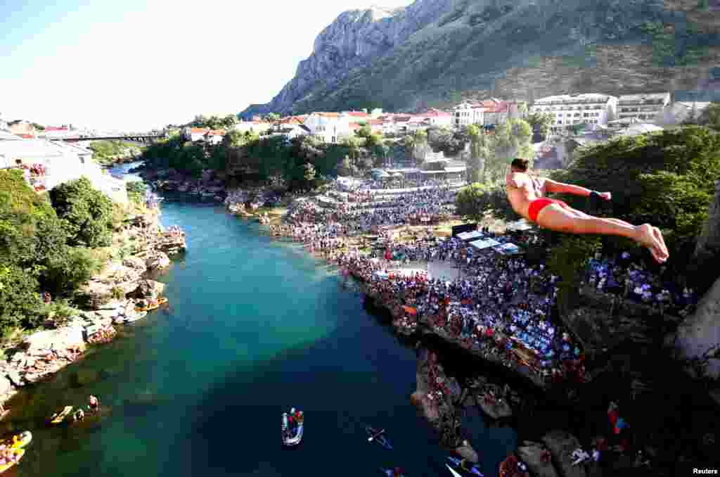 A man jumps from the Old Bridge during 450th traditional diving competition in Mostar, Bosnia and Herzegovina.