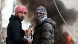 Free Syrian Army fighter look back as they stand in front of a burning barricade during heavy fighting in the Ain Tarma neighborhood of Damascus January 30, 2013.