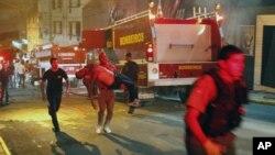 브라질 남부 나이트 클럽 화재 현장에서 한 남자가 부상자를 옮기고 있다.