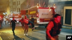 一名男子抱着伤者逃出失火夜总会