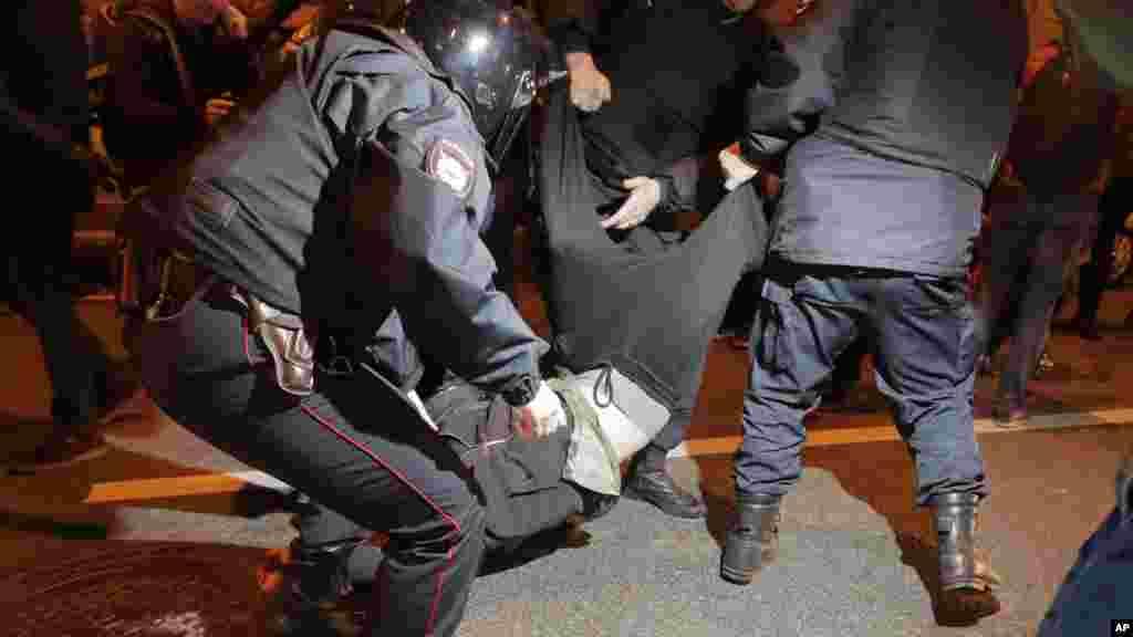 Les policiers anti-émeutes arrêtent un manifestant lors d'un rassemblement à Saint-Pétersbourg, en Russie, le 7 octobre 2017.