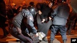 Сотрудники российской полиции задерживают одного из участников протестов