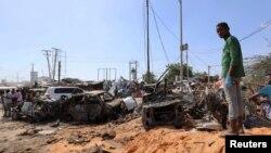 Seorang pria berdiri di lokasi ledakan bom mobil di sebuah pos pemeriksaan di Mogadishu, Somalia, 28 Desember 2019. (Foto: Reuters)