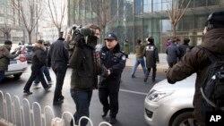 中國政府加大對外國記者的壓制。圖為2014年1月26日,警員阻止在北京的外國記者採訪受審的法律維權人士許志永的辯護律師張慶方。