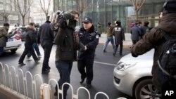 中国政府加大对外国记者的压制。图为2014年1月26日,警察阻止在北京的外国记者采访受审的法律维权人士许志永的辩护律师张庆方。