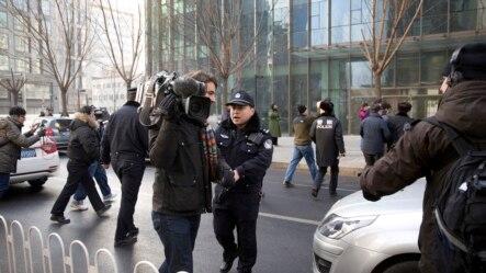 """公盟创办人、宪政学者许志永在2014年1月被北京市第一中级人民法院以""""聚众扰乱公共场所秩序罪""""抓捕,同月26日对其进行审判。图为警察阻止在北京的外国记者采访许志永的辩护律师张庆方。(资料照)"""