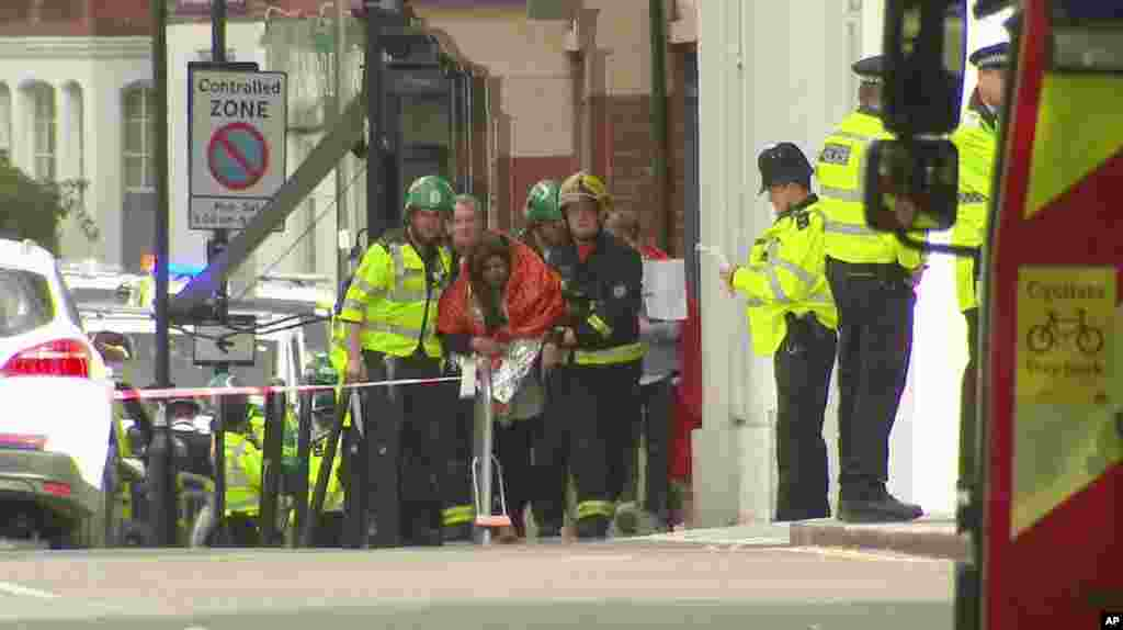 In this image made from video, a woman with blankets wrapped around her is being escorted by emergency services near the scene of an explosion in London Friday, Sept. 15, 2017.
