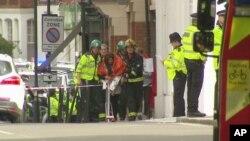 Dalam gambar yang diambil dari video ini, seorang perempuan menyelimuti badannya dengan selimut, dikawal oleh petugas layanan darurat di dekat lokasi ledakan di London, Jumat, 15 September 2017. (Sky via AP)
