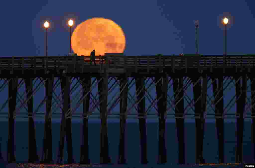 The moon sets in the early morning hours as a man walks along an ocean pier in Oceanside, California.